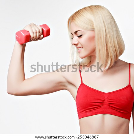 girl with a sports figure does exercises with dumbbell on grey background - stock photo