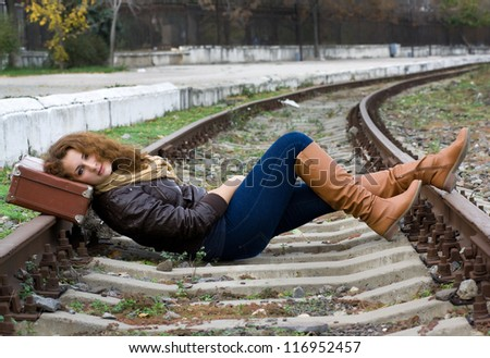 Girl with a suitcase lying on the tracks - stock photo