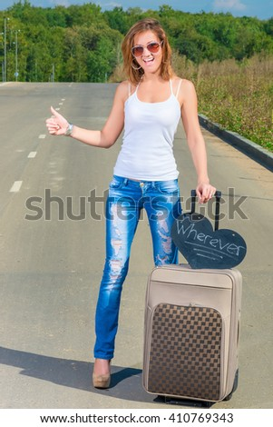 girl with a suitcase on the road traveling hitchhike - stock photo