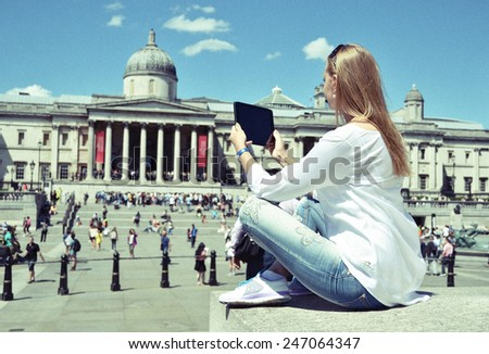 Girl with a tablet on Trafalgar square in London - stock photo