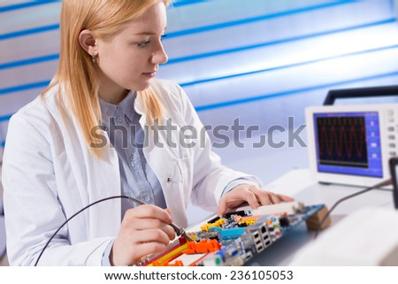 girl with a tester and a printed circuit board - stock photo