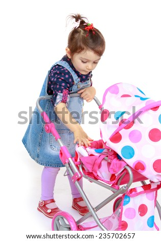 Girl with a toy doll stroller shakes.White background, isolated photo. - stock photo
