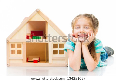 girl with a toy house lying on the floor - stock photo
