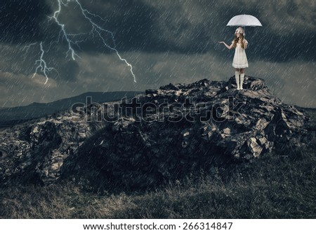 Girl with a white umbrella stands on the top of a mountain during a severe thunderstorm. - stock photo