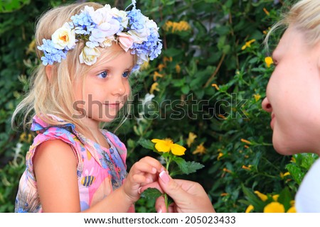 girl with a wreath of flowers look at mom - stock photo