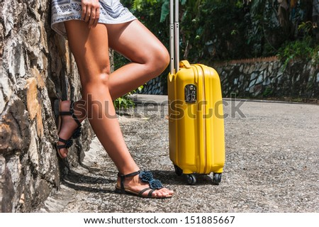 Girl with a yellow suitcase on a resort in Thailand - stock photo