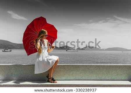 Girl with an umbrella against the sea in Thailand - stock photo