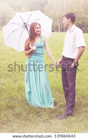 girl with an umbrella and boy holding hands - stock photo