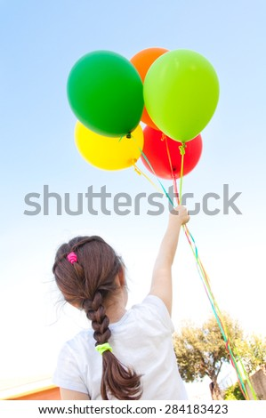 Girl with balloons flying in the sky - stock photo