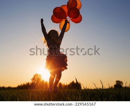 girl with balloons jumping outdoor - stock photo