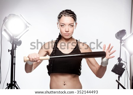 girl with baseball bat in a studio - stock photo