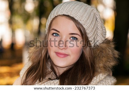 girl with beautiful blue eyes in park in the fall - stock photo