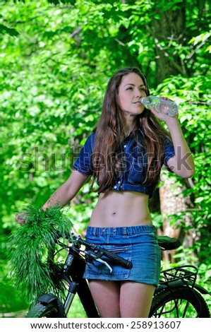 Girl with bicycle in the woods. Smiling and drinking water - stock photo