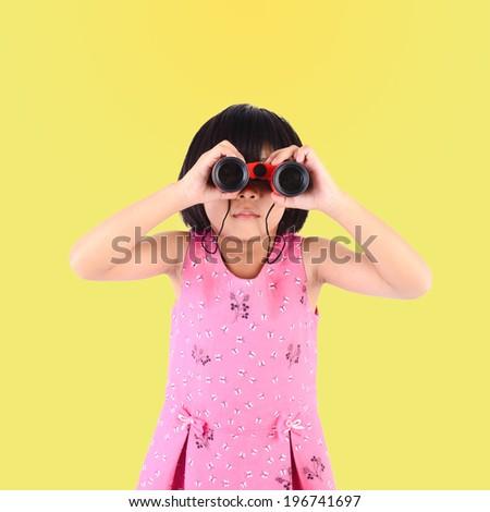Girl with binoculars with yellow background - stock photo