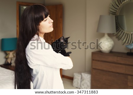 Girl with black hair style holding black cat in hands standing in bedroom interior. Relax and comfort at home - stock photo