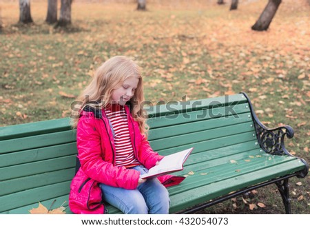 girl with book in autumn park - stock photo