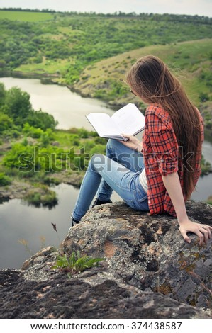 Girl with book, sitting on the rock above river - stock photo