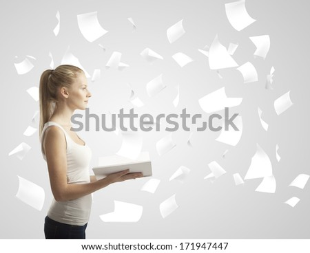 girl with book with flying around paper - stock photo