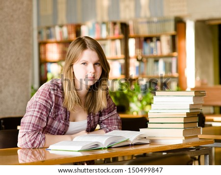 girl with books at the library. looking at camera - stock photo