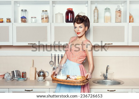 Girl with Cake and milk standing in the kitchen. - stock photo