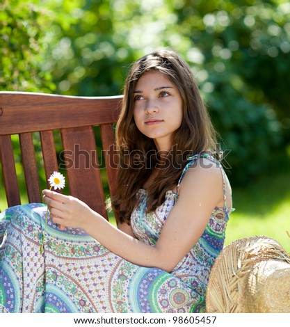 Girl with camomile or oxeye daisy flower sitting outdoor in summer day - stock photo