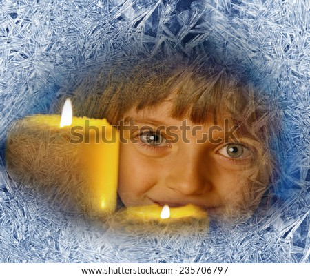 girl with candles looking through a frosted window - stock photo