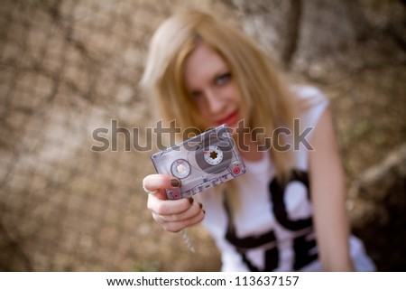 Girl with cassette near the fence - stock photo
