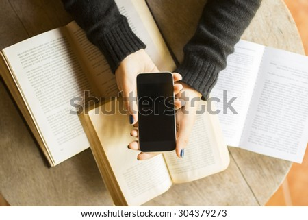 Girl with cell phone and books - stock photo