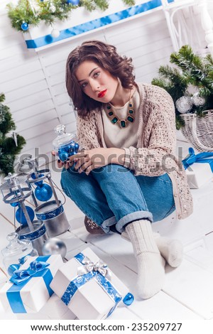 girl with Christmas gifts thoughtfully looking at the camera - stock photo