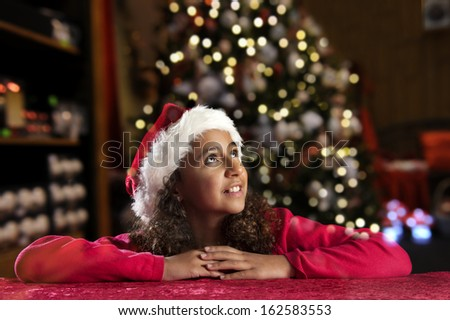 Girl with christmas hat  on black background - stock photo