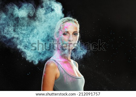 girl with colored powder exploding around her and into the background. - stock photo