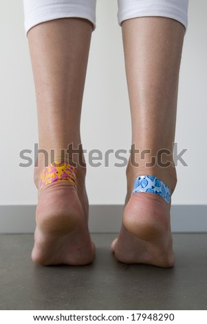 girl with colorful adhesive plasters on the blisters on her heels - stock photo