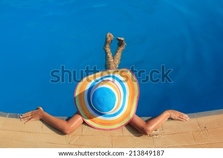 Girl with colorful hat in the pool - stock photo