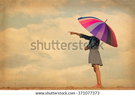 Girl with colorful rainbow umbrella pointing forward, grunge vintage filter. - stock photo