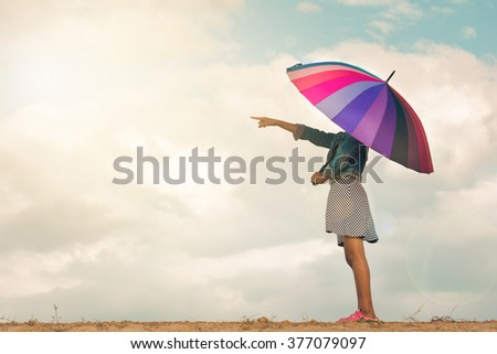 Girl with colorful rainbow umbrella pointing forward, vintage filter. - stock photo