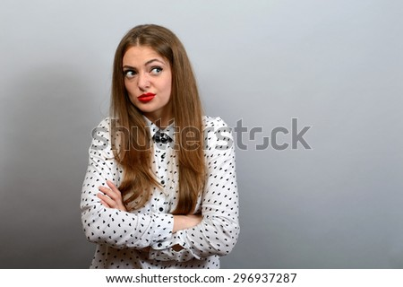 Girl with condemning glance, crossed hands on grey background - stock photo