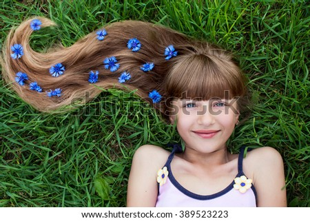 Girl with cornflowers in her long hair lying on the grass - stock photo