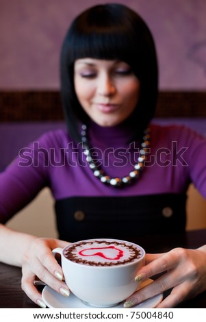 girl with cup of coffee, focus on coffee - stock photo