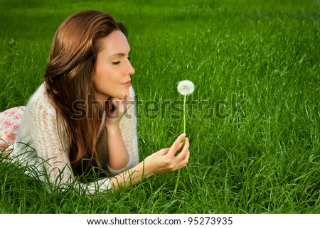 Girl with dandelionson green field - stock photo