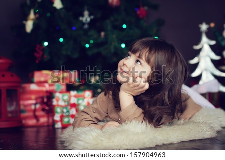girl with dark hair lying on the carpet. Christmas tree in the background. smiles - stock photo