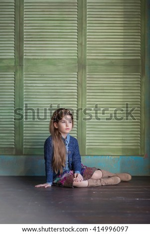 girl with decoration in her hair in a blue denim shirt, sweater and skirt colorful skirt and boots karichnevyh karichnevom sitting on wooden floor near the wooden wall and looks out the window - stock photo