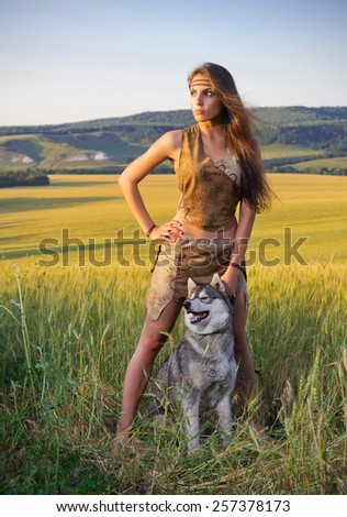 Girl with dog  in a wheat field at sunset - stock photo