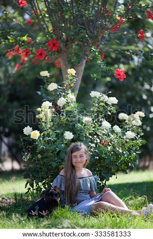 Girl with dog in garden - stock photo