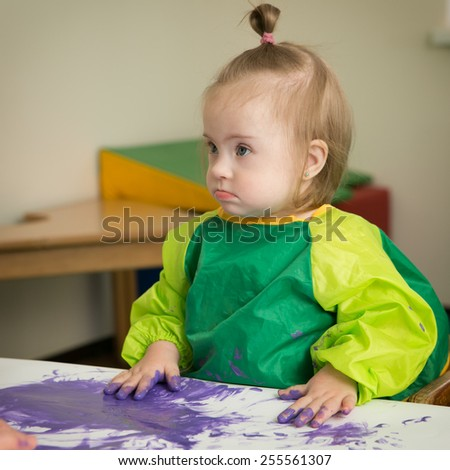 Girl with Down syndrome draws fingers paint - stock photo