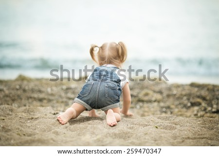Girl with Down syndrome funny crawling on the beach - stock photo