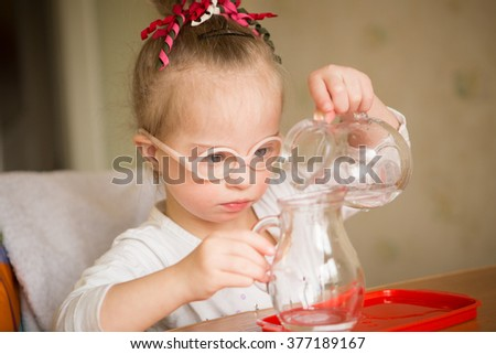 Girl with Down syndrome gently pours water from a jug into a jug - stock photo