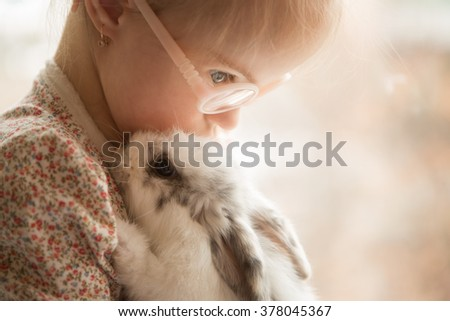 Girl with Down syndrome hugs rabbit - stock photo