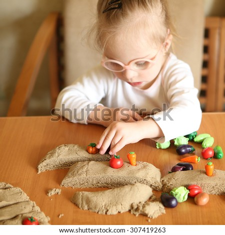 Girl with Down syndrome is involved in sorting vegetables - stock photo