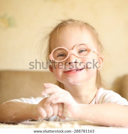 Girl with Down syndrome playing flour - stock photo