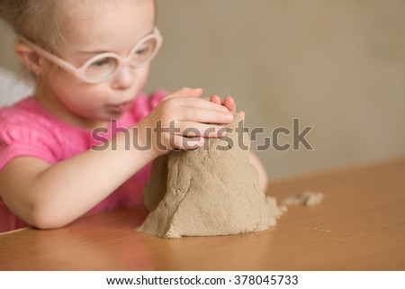 Girl with Down syndrome playing kinetic sand - stock photo